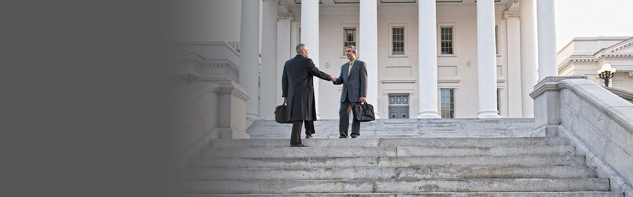 Image of two men shaking hands in front of a government building