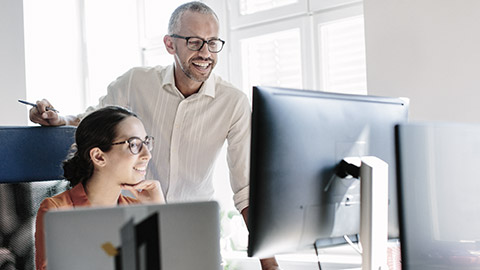 Image of a man and woman using a computer in an office setting