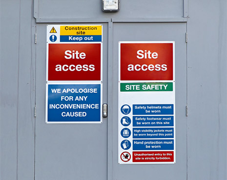 Image of a selection of safety signs hung on a door